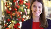 Рождественский подарок : Portrait of cheerful young woman near decorated Christmas tree. Pretty female standing and smiling. New Year celebration Стоковые видеозаписи