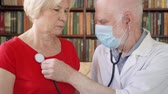 сердцебиение : Male professional doctor at work. Senior man physician in white coat and medical mask using stethoscope for listening sick senior female patients lungs and measuring heart rate in modern at home Стоковые видеозаписи
