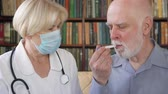 вирус : Female professional doctor in medical mask at work. Senior woman physician measuring temperature to sick senior male patient by thermometer at home. Consulting about treatment and therapy