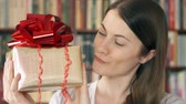 knihovna : Cheerful smiling young woman standing at home with present. Female holding golden gift box with red ribbon celebrating birthday. Making funny faces. Bookcase bookshelves in background