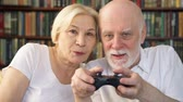 controlador : Senior couple gamers playing video games at home. Addicted senior players with remote controller of game console. Cybersport for active modern elderly people