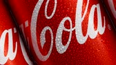 estanho : MOSCOW, RUSSIA- CIRCA MARCH 2018: Cold red cans of popular american sort drink with Coca-Cola logo diagonal dolly tracking shot. Worldwide famous soda cans with drops of water. Front view Stock Footage