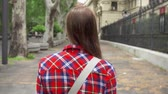 Рим : Young carefree woman in red shirt walking down european street in slow motion. View from behind of female enjoying vacation in Rome alone. Student traveling through Europe