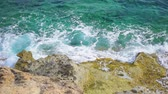 ниже : Aerial ocean view of turquoise sea at sunny day. Top view of seawater waves splashing against old moldy rocks in slow motion