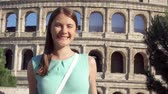 coliseum : Young woman standing on background of famous Roman attraction Colosseum in Rome, Italy in slow motion. Happy female tourist enjoying her european summer vacation. Student travel through Europe