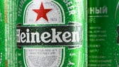 ebilmek : MOSCOW, RUSSIA- CIRCA MARCH 2018: Cold green cans of popular dutch beverage with Heineken logo rotating. Worldwide famous beer cans with drops of water. Seamless loopable