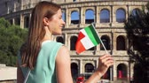coliseum : Young woman standing near famous attraction Colosseum in Rome, Italy. Teenage girl waving Italian flag in slow motion. Happy female tourist enjoying european vacation. Student travel through Europe