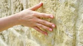 tactile : Woman sliding hand against old ancient stone wall in slow motion. Female hand touching hard rough surface of rock on sunny summer day Stock Footage