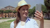 римский : Young woman walking on Circus Maximus and using mobile phone in slow motion in Rome, Italy. Happy female traveler enjoying vacation in european city. Smiling girl having video chat via online app Стоковые видеозаписи