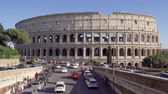 kolosszeum : ROME, ITALY - CIRCA May 2018: Panorama of famous attraction Colosseum in Rome, Italy. Veiw from road on ancient Flavius amphitheater Coliseum. Tourists walking and cars passing by Stock mozgókép