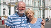 Portrait of happy senior couple standing on Palace Square looking at camera. Happy loving pensioners traveling in Saint Petersburg, Russia. Winter Palace on background. Hand-held camera