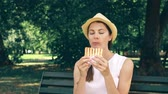 Hungry young woman in white shirt sitting on bench and eating grilled sandwich with ham in public park. Tourist in hat having lunch in garden enjoying summer sunny day. Green trees on background