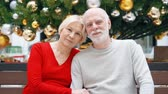 Portrait of senior couple sitting in mall looking at camera during holiday season. Loving hugging pensioners in shopping center smiling. Christmas tree with decorations on background. Hand-held camera
