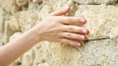 Woman sliding hand against old ancient stone wall in slow motion. Female hand touching hard rough surface of rock on sunny summer day Stok Video