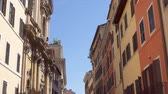 Beautiful european urban architecture. Cozy colorful italian street. Exterior of old residential buildings in center of Rome, Italy. Camera moving up in slow motion Stok Video