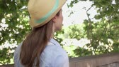 Young woman in hat walking along waterfront in slow motion. Behind view of happy female traveler enjoying vacation outdoors. Concept of new experience and freedom in traveling