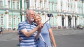 vôo : Senior couple on Palace Square do selfie with mobile phone and and self-stick on vacation. Happy loving pensioners travel in Saint Petersburg, Russia. Winter Palace on background. Hand-held camera