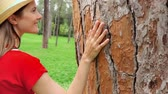 sentir : Woman in red dress and hat sliding hand along big old tree in slow motion. Female hand touching green crust surface of tree trunk