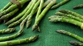 officinalis : Raw garden asparagus stems. Fresh green spring vegetables on jute background. (Asparagus officinalis) Stock Footage