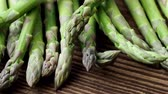 officinalis : Raw garden asparagus stems. Fresh green spring vegetables on wooden background. (Asparagus officinalis). Stock Footage