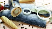 śledź : Saltwater marinated fish, cold appetizer. Herring fillet marinated on wooden cutting board