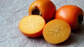 азиатская кухня : Whole and half of fresh ripe persimmons. Japanese persimmon (Diospyros kaki) Стоковые видеозаписи