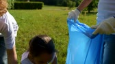 voluntário : Scaled up look on children cleaning trash in park