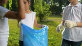 voluntário : Charming kids working together while picking up garbage in park