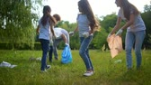 voluntário : Cheerful kids helping volunteers with picking up plastic bottles outdoors