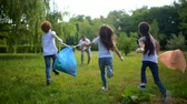 voluntário : Children running to volunteers with trash bags with plastic bottles Vídeos