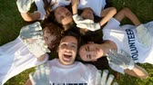 voluntário : Multi aged volunteers laying on grass and waving into camera Vídeos