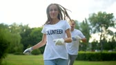 voluntário : Cheerful volunteers and children running and smiling into camera
