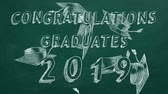 greenboard : Hand drawing text Congratulations graduates. 2019. and graduation caps on green chalkboard.