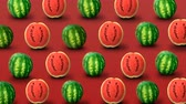 スイカ : Fresh watermelons on red background. Colorful fruit pattern. 4k video.