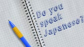 memorando : Do you speak Japanese? Text handwritten on sheet of notebook and animated.