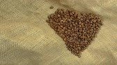 sackcloth : A step motion dedicated to the love of coffee. The cup moves while the beans are going to form an heart Stock Footage