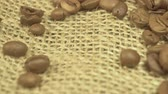 makro : Top view of messy pile of freshly roasted brown coffee beans on textured canvas textile