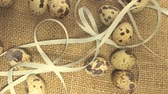 egg painted : Easter eggs with a ribbon on a rag background with straw Stock Footage