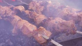 Top View of Preparing Shish Kebabs on Skewers over a Fire in Nature. Cooking kebabs on skewers over a fire in the countryside in the village. Raw meat is cooked on charcoal grill. Preparation of a