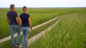 países : Slender man and woman in jeans go on the forest road in the field among high green grass and admire nature at sunset.