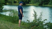 não barbeado : A slender gray-haired man in a blue t-shirt, cap and glasses walks barefoot on the green grass on the river Bank on a summer day, stretches and admires nature.