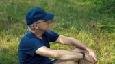 não barbeado : A slender, serious gray-haired man in a blue t-shirt, cap and glasses sits on the green grass in the forest on a summer day, looks into the distance and thinks. Vídeos