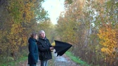пожилые : A slender, gray-haired man with glasses and a slender, pretty, middle-aged woman walk along an autumn Park Avenue under a black umbrella, admiring nature, talking and smiling.