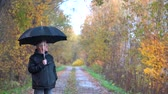 пожилые : A slender man with gray hair, wearing glasses and a black jacket with a black umbrella in his hands walks in the afternoon along the autumn Park Avenue and admires the autumn trees.