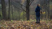 eikenblad : A slender woman in a blue jacket and with a backpack on her shoulder stands on the edge of a ravine in the autumn forest and looks at a tall dry oak on a cloudy day. Stockvideo