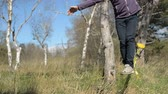 slackliner : Close-up A man dressed in a hat and beard, stands up to walk in the wind against the background of the Caucasus mountains of the blue sky and clouds Stock Footage