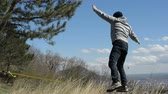 slackliner : A man dressed in a hat and beard, stands up to walk in the wind against the background of the Caucasus mountains of the blue sky and clouds