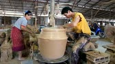 crock : Feb 24, 2017 - Ratchaburi, Thailand: Time lapse, skillful craftsman and his assistant works on clayed pot in pottery industry of Ratchaburi province. They work for Charoendinthai Pottery.