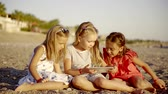 flatbed : cute little girlies are watching video in an application of a tablet, sitting on an empty beach Stock Footage