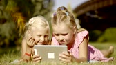 flatbed : two little friends are looking at a display of a tablet, lying on a grass in a backyard in sunny day